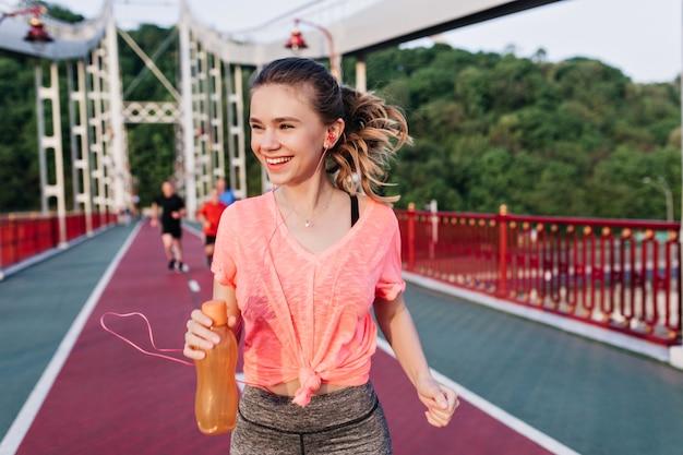 Ragazza bionda di risata che tiene una bottiglia di succo e che corre lungo la pista di cenere. incredibile modello femminile divertendosi allo stadio.