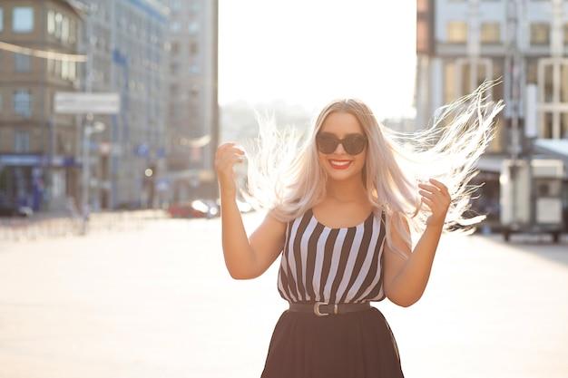 Смеющаяся блондинка с ветром в волосах позирует с мягким солнечным светом. место для текста