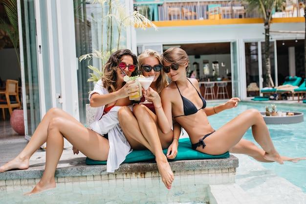 Donna bionda di risata che celebra con le vacanze estive di amici e bere cocktail. tre modelli femminili che si rilassano insieme in piscina in una giornata calda.