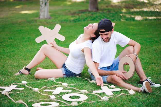 公園で三目並べをしている笑う男の子と女の子。