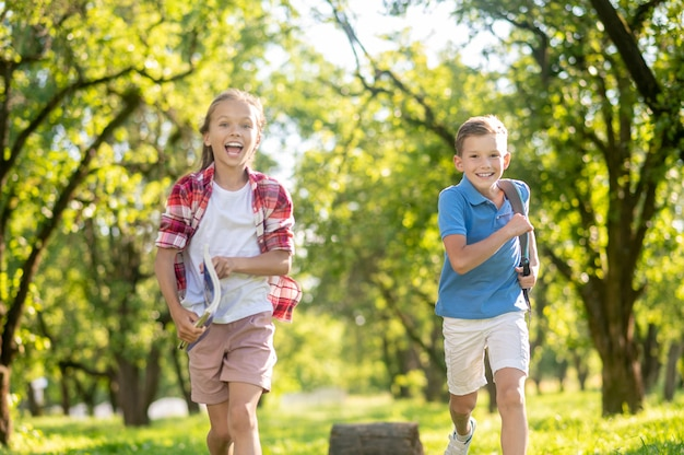 Laughing boy and girl running in park