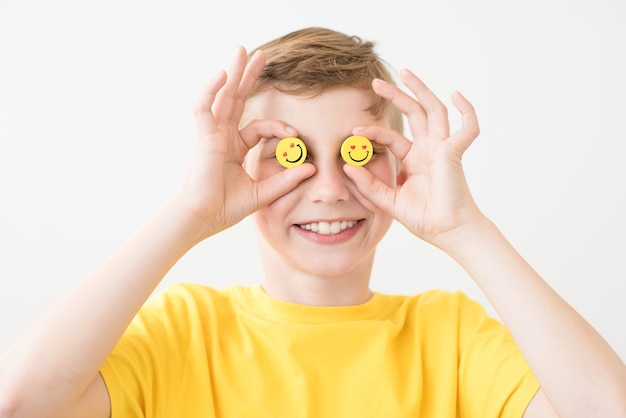 目の代わりに面白い黄色のスマイリーを手に持って笑う少年
