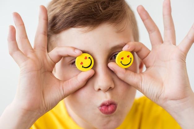目の代わりに面白い黄色のスマイリーを手に持った笑う少年