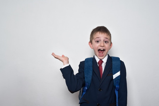 Смеющийся мальчик в школьной форме на белой поверхности держит руку.