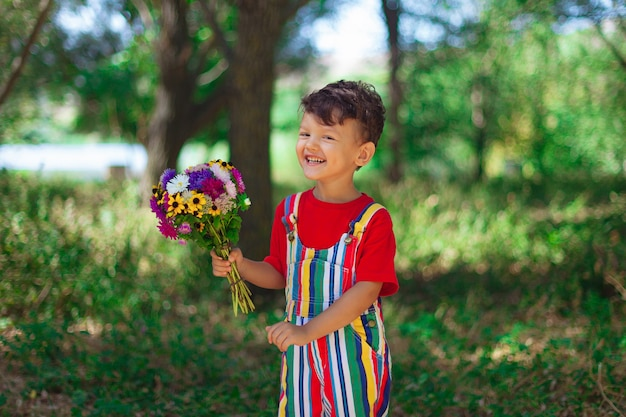 Laughing boy with a bouquet of flowers a child with a bouquet of wild flowers for mom a gift a surpr...