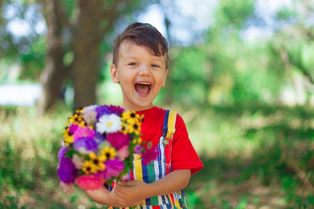 Laughing boy with a bouquet of flowers a child with a bouquet of wild flowers for mom a gift a surprise with their own hands emotional kid with flowers in bright clothes in nature