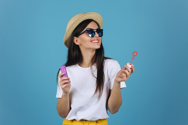 Laughing brunette girl in summer hat and sunglasses has fun with soap balloons