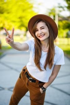 晴れた朝を楽しんでいる公園に立っている流行の服を着て薄い肌で笑うブルネットの少女。公園の路地の近くでポーズをとって帽子と白いtシャツを着た絶妙な若い女性の肖像画。