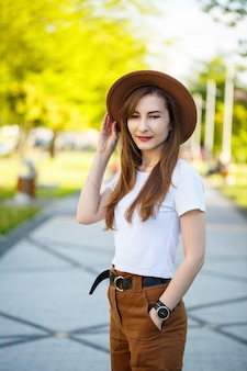 Laughing brunette girl with pale skin wearing trendy clothes standing in a park enjoying a sunny morning. portrait of an exquisite young lady in a hat and white t-shirt posing near a park alley.