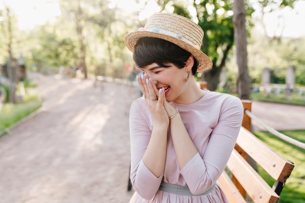 Ragazza castana di risata con pelle pallida che indossa gioielli alla moda che si siede sulla panca di legno nel parco, godendo la mattina di sole