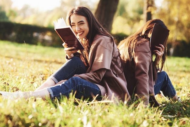 Laughing brunette twin girl sitting back to back on the grass with her sister, who is covering face with brown book, wearing casual coat in autumn sunny park on blurry background.