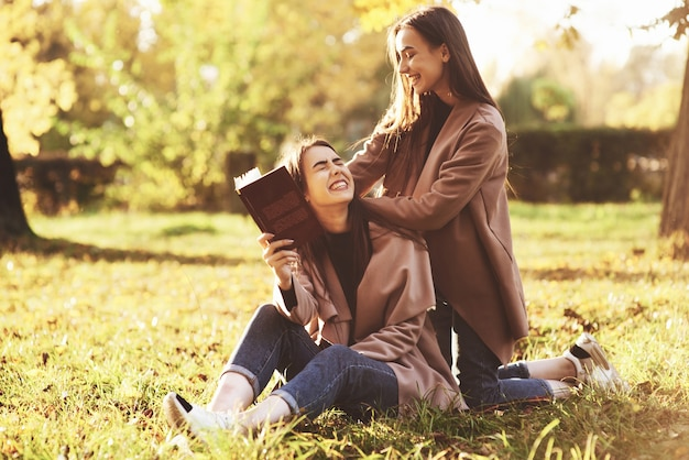 Laughing brunette twin girls sitting on the grass. one of them is holding brown book, onother one is leaning on sisters shoulders with her hands from the back in autumn sunny park on blurry background