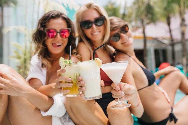Смеющаяся брюнетка женщина в розовых очках празднует что-то с друзьями во время летнего отдыха. красивые загорелые дамы пьют коктейли и наслаждаются отдыхом.