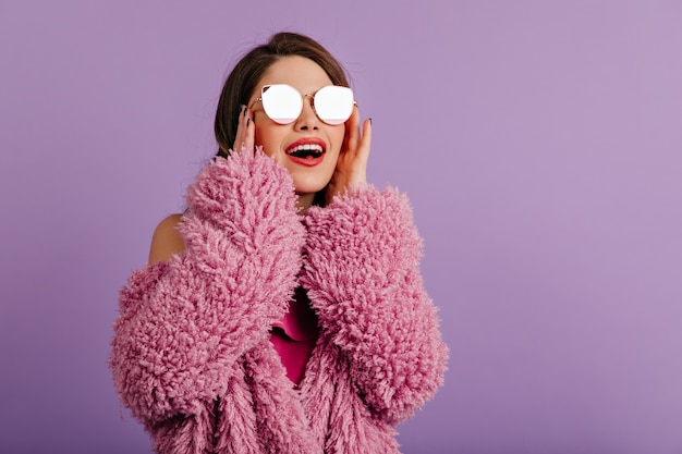 Laughing brunette woman touching her sunglasses