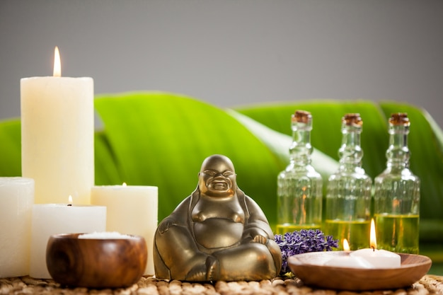 Laughing buddha figurine, lit candle, massage oil bottles and sea salt
