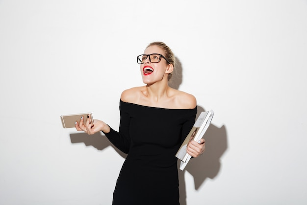 Laughing business woman in dress and eyeglasses looking up
