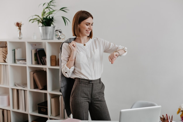 Laughing business woman in white blouse and gray pants is looking at wrist watch, standing against of office furniture.