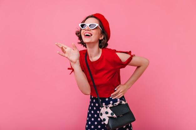 短い散髪ポーズでのんきな女の子を笑う。笑顔のベレー帽の感情的なフランスの白人女性。