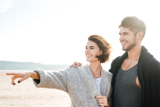 Laughing casual couple standing at the beach and pointing finger away