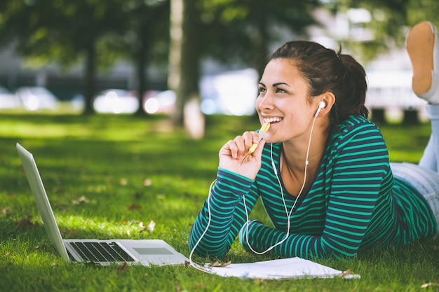 Laughing casual student lying on grass taking notes