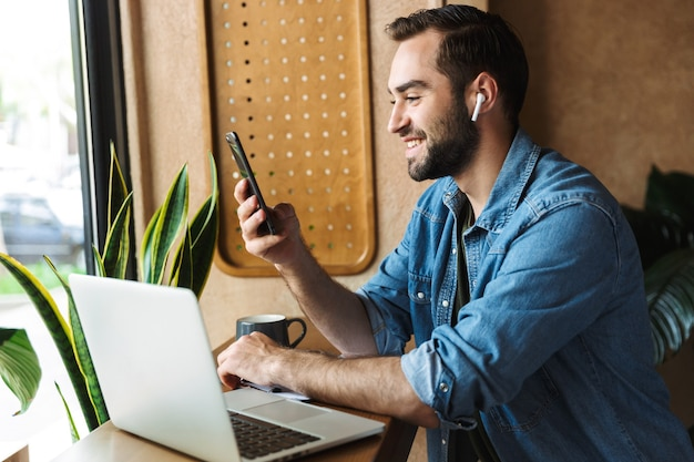 Laughing caucasian man wearing denim shirt using earpod and cellphone with laptop while working in cafe indoors
