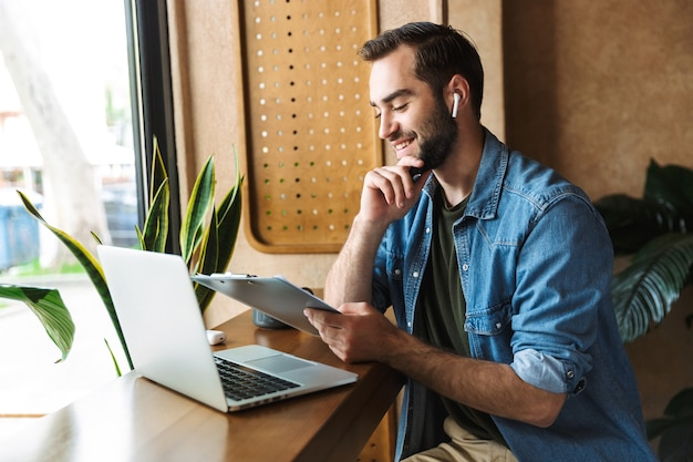 Laughing caucasian man wearing denim shirt using earpod and clipboard with laptop while working in cafe indoors