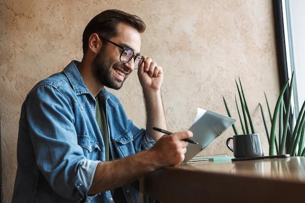 Смеющийся кавказский мужчина в очках читает документы и пьет кофе во время работы в кафе в помещении