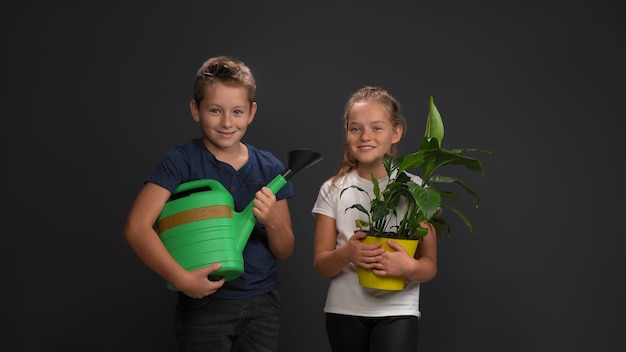 Laughing caucasian teenagers, a boy holding a watering can, a girl holding a plant in a flowerpot.
