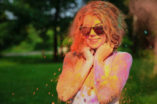 마른 holi 페인트로 덮여 안경을 쓰고 웃는 백인 여자