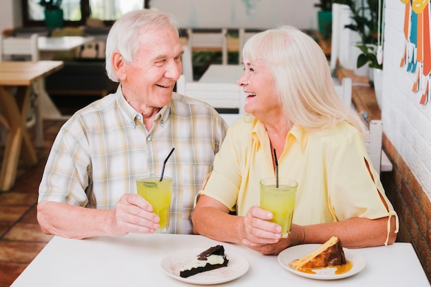Laughing celebrating elderly couple in cafe