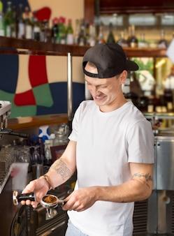Смеется веселый бариста или бармен, держащий портфильтр, наполненный молотым кофе.