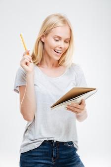흰 벽에 고립된 아이디어로 노트북을 들고 웃고 있는 쾌활한 예쁜 소녀