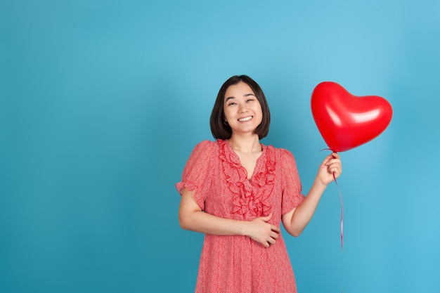 Laughing, cheerful young asian woman holds a flying red heart-shaped balloon
