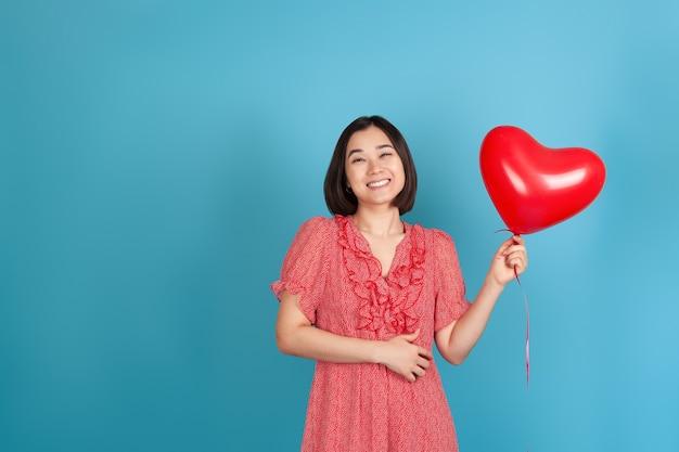 笑って、陽気な若いアジアの女性は飛んでいる赤いハート型の風船を持っています