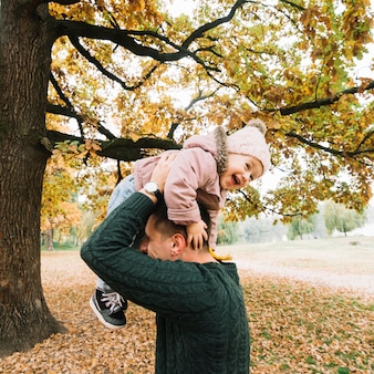 Laughing child and dad playing in autumn park