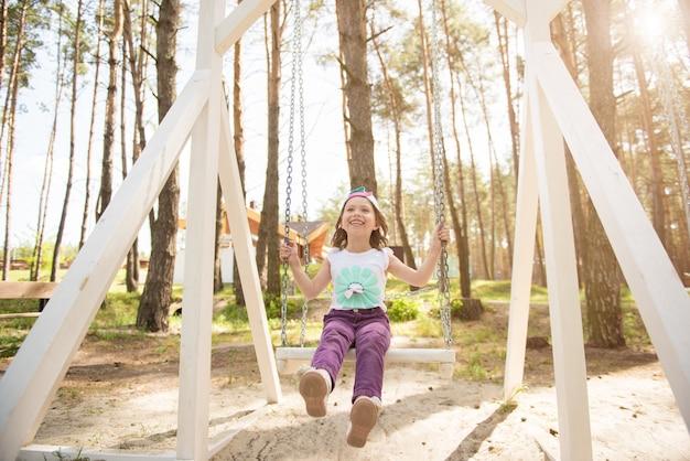 여름 공원에서 스윙에 웃는 아이