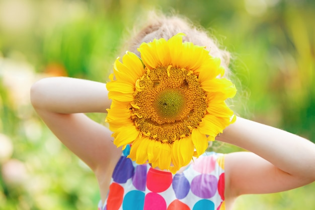 Laughing child with holds sunflower