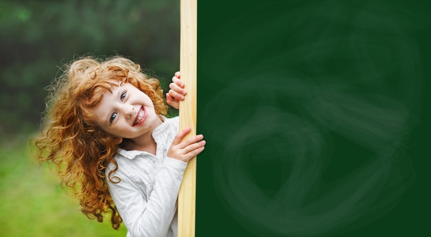 Laughing child with school blackboard showing healthy white teeth.