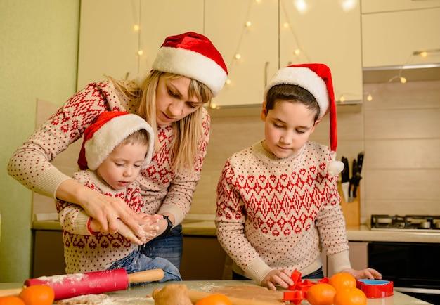 웃는 아이들은 맛있는 진저 쿠키를 굽습니다. 크리스마스 과자를 굽고 여성 및 작은 소년.