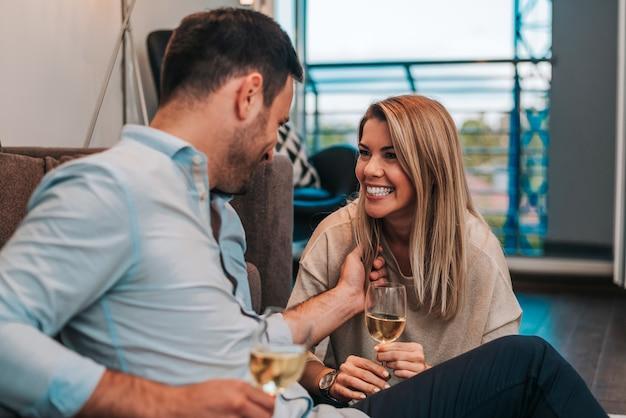 Laughing couple enjoying white wine while sitting on the floor.