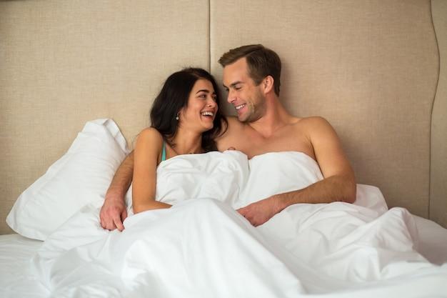 Смеющаяся пара в постели.