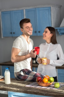Laughing couple in at the kitchen in the morning.