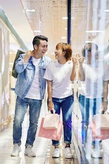 店の窓を見て笑っているカップル