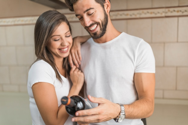 Laughing couple looking at wine bottle