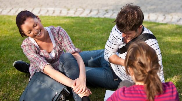 彼らの大学キャンパスで女性の友人と話す草の根に座っている学生のカップルを笑う