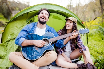 Laughing couple playing guitar
