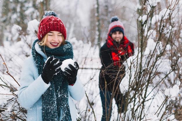 Смех пара, играя снежки в лесу