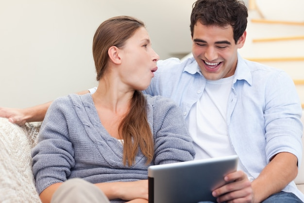 タブレットコンピュータを使ってカップルを笑う