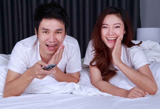 Laughing couple watching movie on bed in bedroom