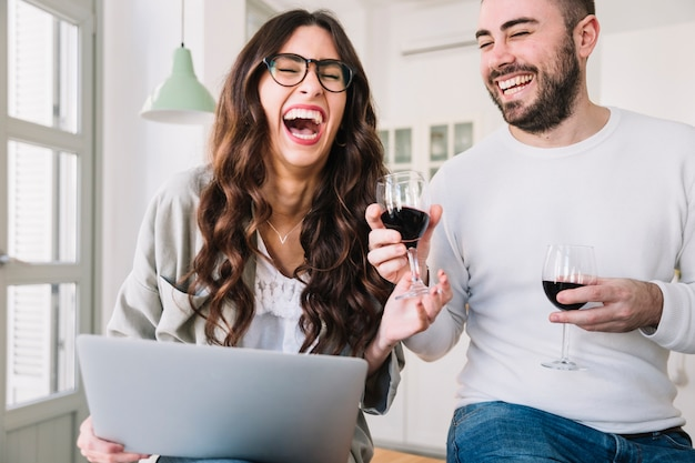 Laughing couple with wine and notebook